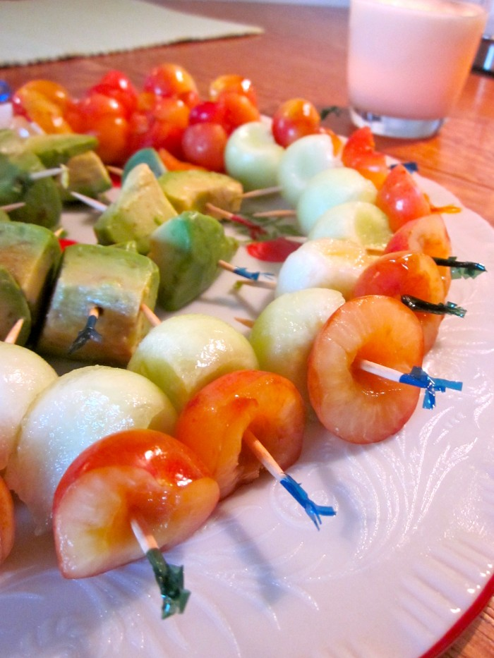 Skewers with cherries, melon, and avocado on plate.