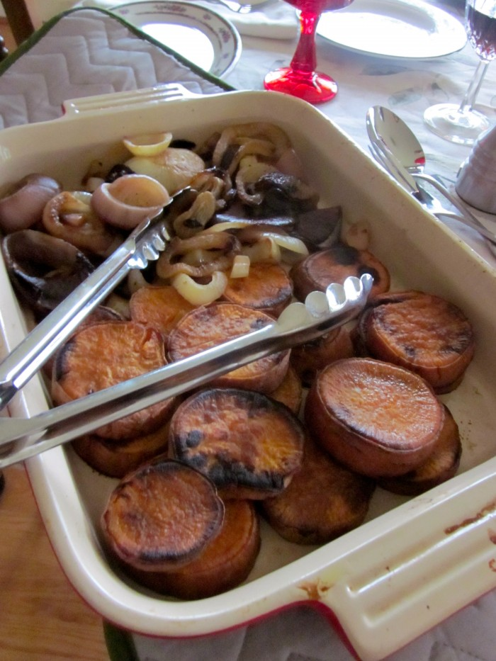 Grilled sweet potato slices and onions in casserole dish with tongs.