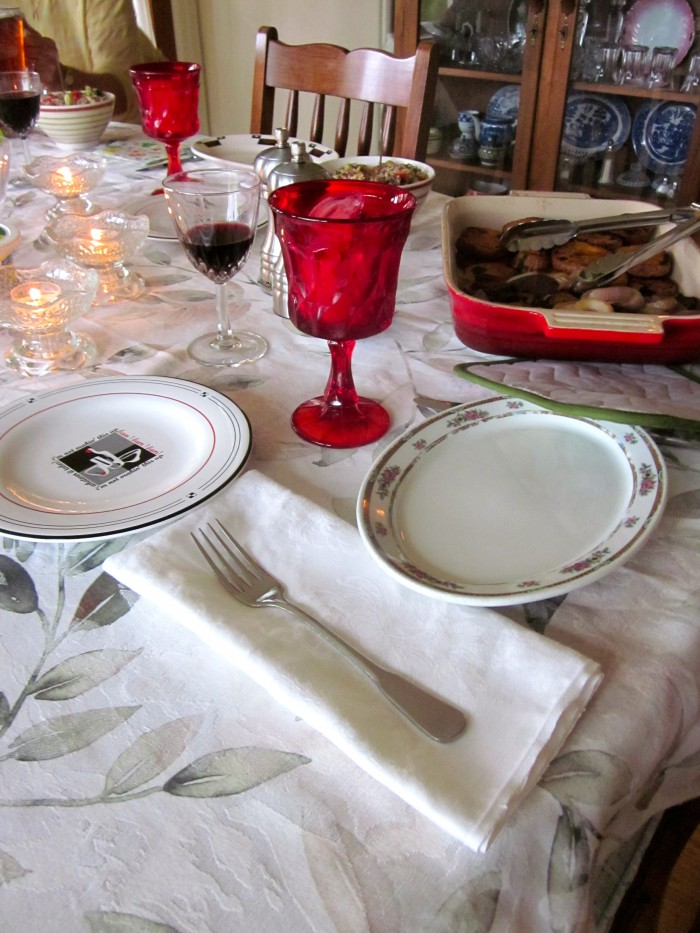 Dinner plates, water glasses, and wine on a dining table with candles.