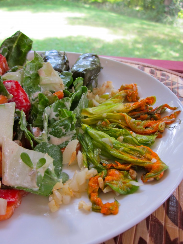 How to cook squash blossoms. Sauteed squash blossoms on plate with salad and dolmas. An easy side dish.