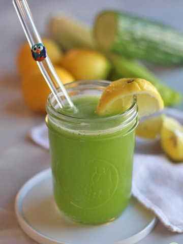Celery cucumber juice in glass with wedge of lemon.