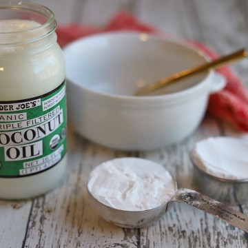 Ingredients for coconut oil deodorant on table: cornstarch, baking soda, and jar of coconut oil.