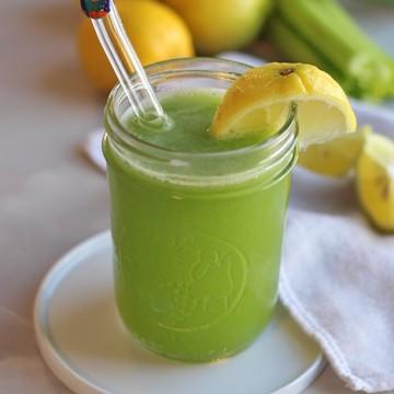 Cucumber celery juice in glass with lemon wedge.