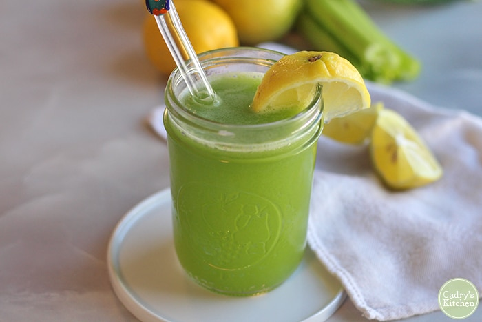 Cucumber celery juice in glass with lemon wedge.