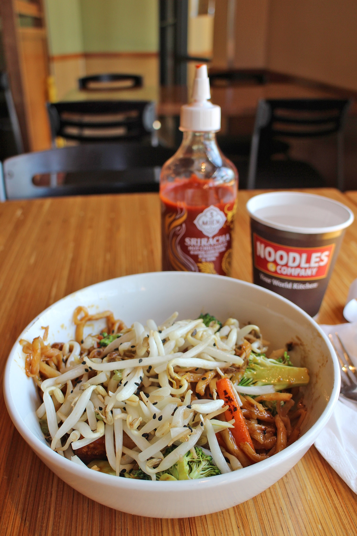 Bowl with Japanese pan noodles, sriracha, and paper cup at Noodles & Company.