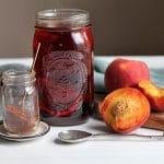 Mason jar with rooibos tea & cut peaches on table.
