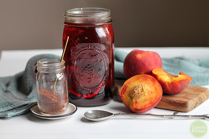 Mason jar with rooibos tea & cut peaches on table.
