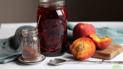 Rooibos tea steeping in a mason jar, cut fresh peaches.