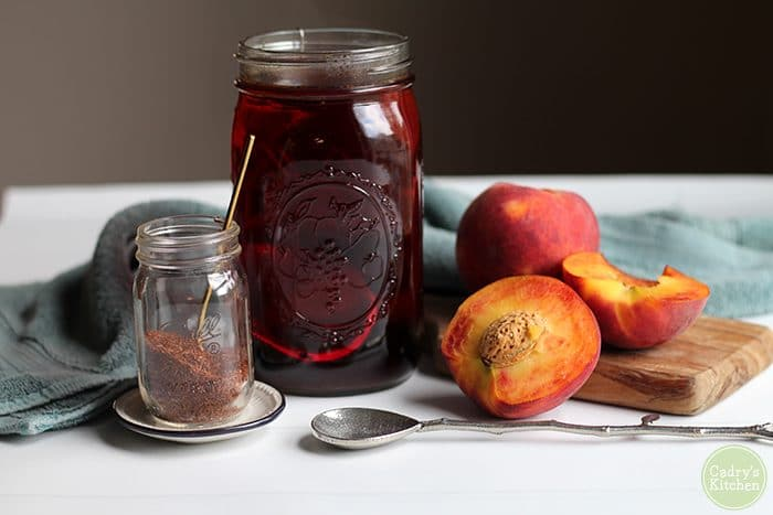 Rooibos tea steeping in a mason jar, cut fresh peaches.