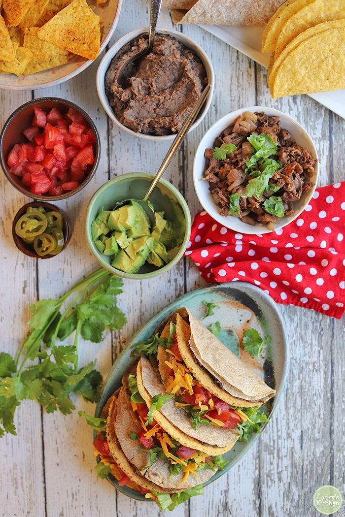 Overhead refried beans, tomatoes, avocado, and tacos.