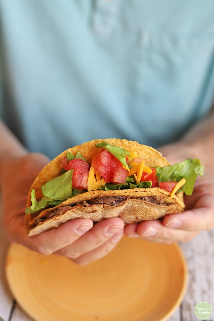 Hands holding a crunchy hard shell taco wrapped in a soft tortilla.