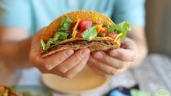 Hands holding a vegan double decker taco, topped with lettuce, tomato, and non-dairy cheese.