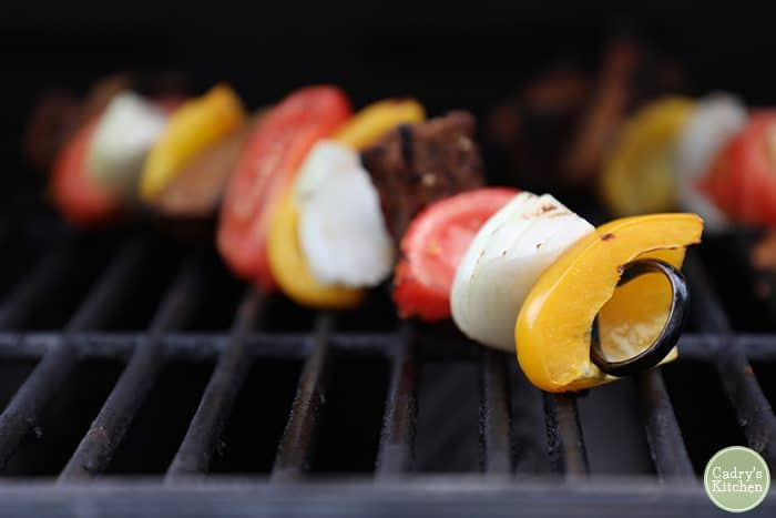 Grilled vegetable skewers on outdoor grill grate
