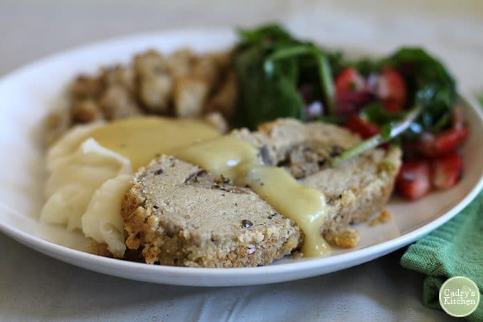 Vegan Thanksgiving plate with Trader Joe's roast, mashed potatoes, gravy, and salad.