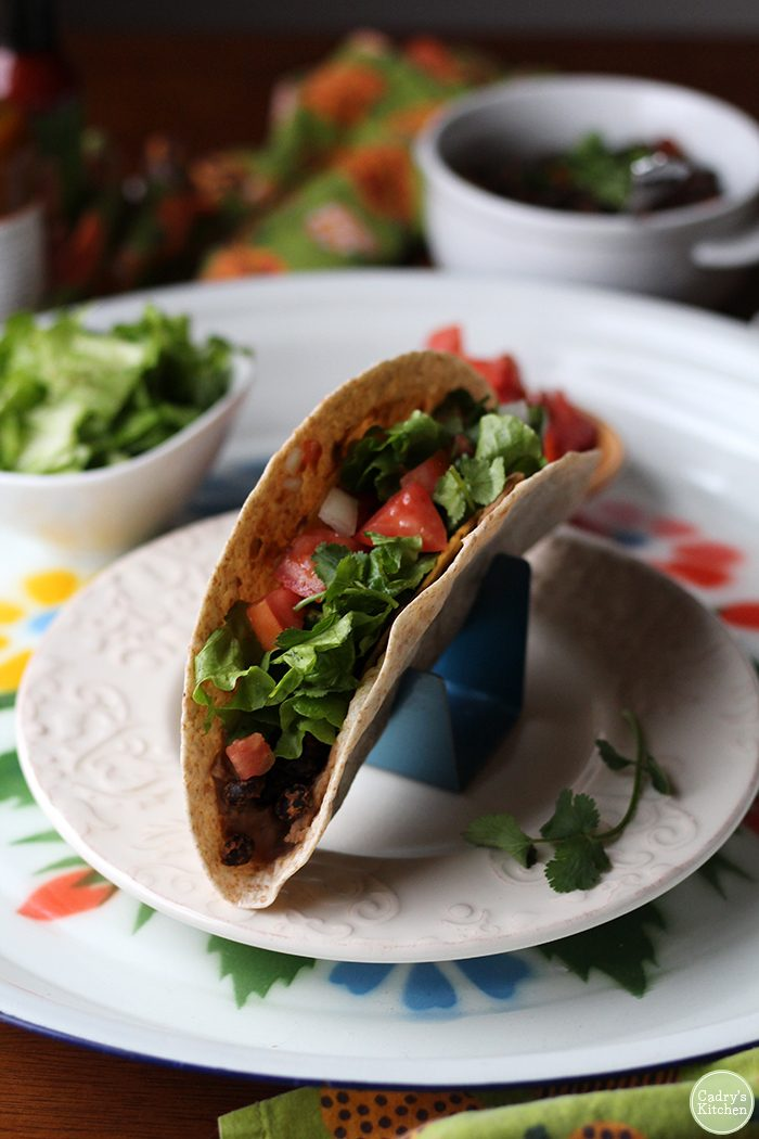 Vegan double decker tacos: Two layers of taco goodness with a soft shell smothered in refried beans, a hard corn shell for crunch, and black beans for filling. So delicious! | cadryskitchen.com