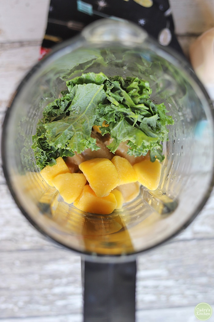 Overhead glass blender with kale, mango, and bananas inside.