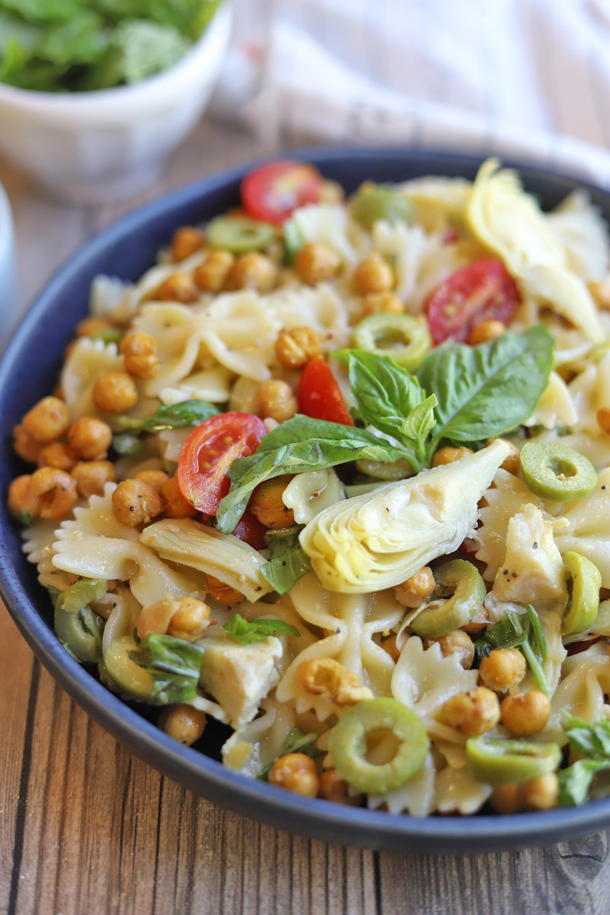Pasta salad with fresh basil in blue bowl.