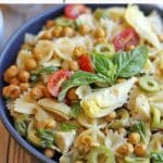 Text overlay: Bowtie pasta salad with chickpeas and artichokes. Close-up salad in bowl.