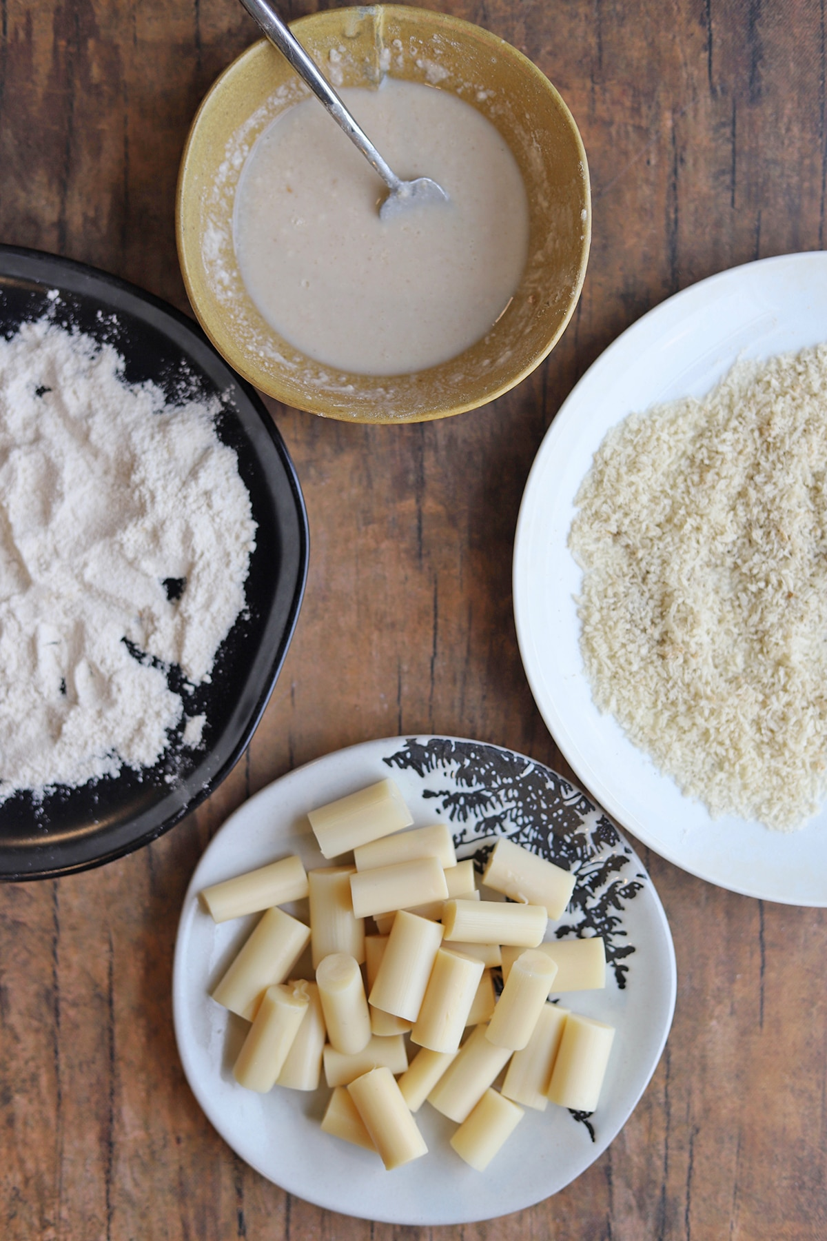 Breading station with hearts of palm, breadcrumbs, non-dairy milk, and flour.
