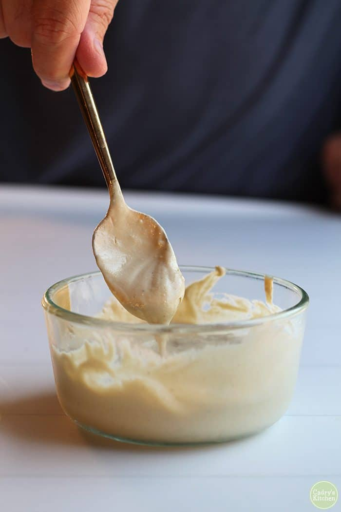 Cashew cream in Pyrex with gold spoon dipping into it.