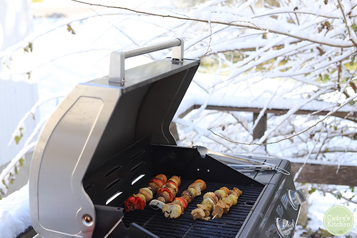 Holiday kebabs on the grill outside in the snow.