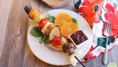 Vegan skewer on plate with cranberry sauce and persimmon salad.