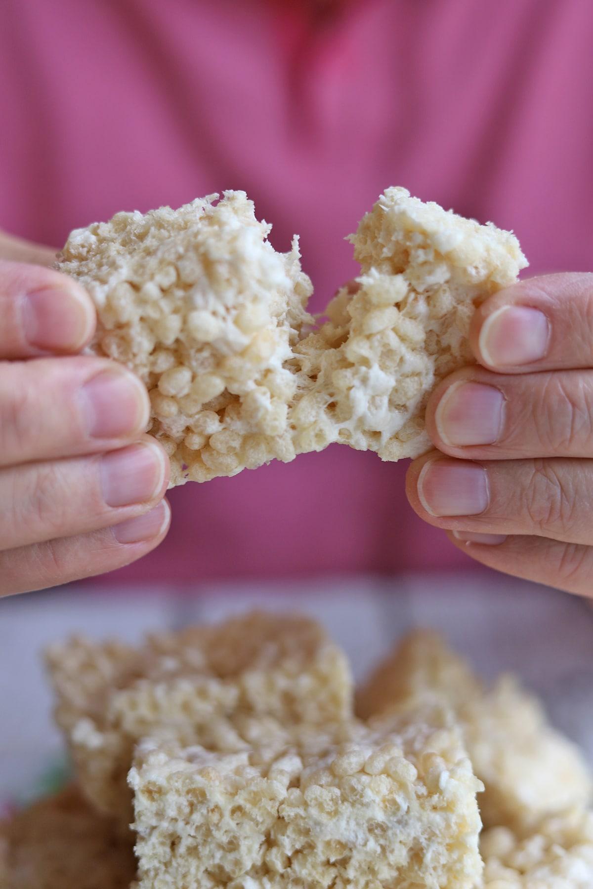 Hands pulling apart vegan rice krispie treat.