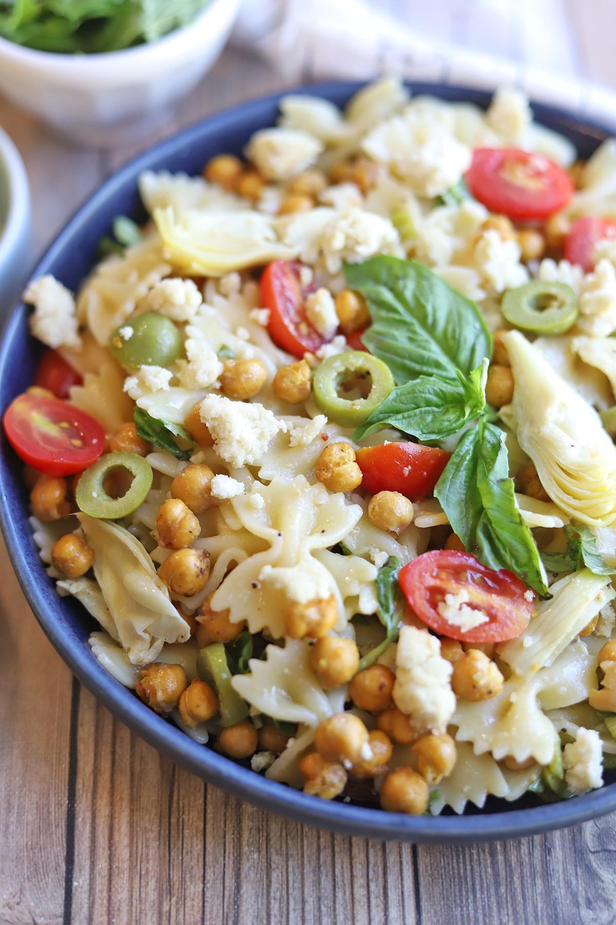 Close-up blue bowl with bowtie pasta salad.