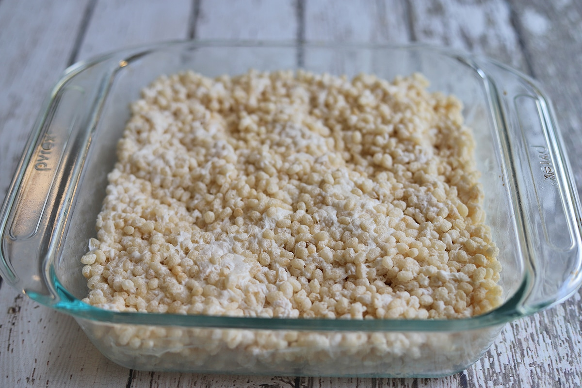 Marshmallow and rice cereal mixture pressed into glass baking dish.