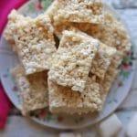 Text overlay: Vegan rice crispy treats. Overhead platter of rice crispy treats on table by marshmallows.