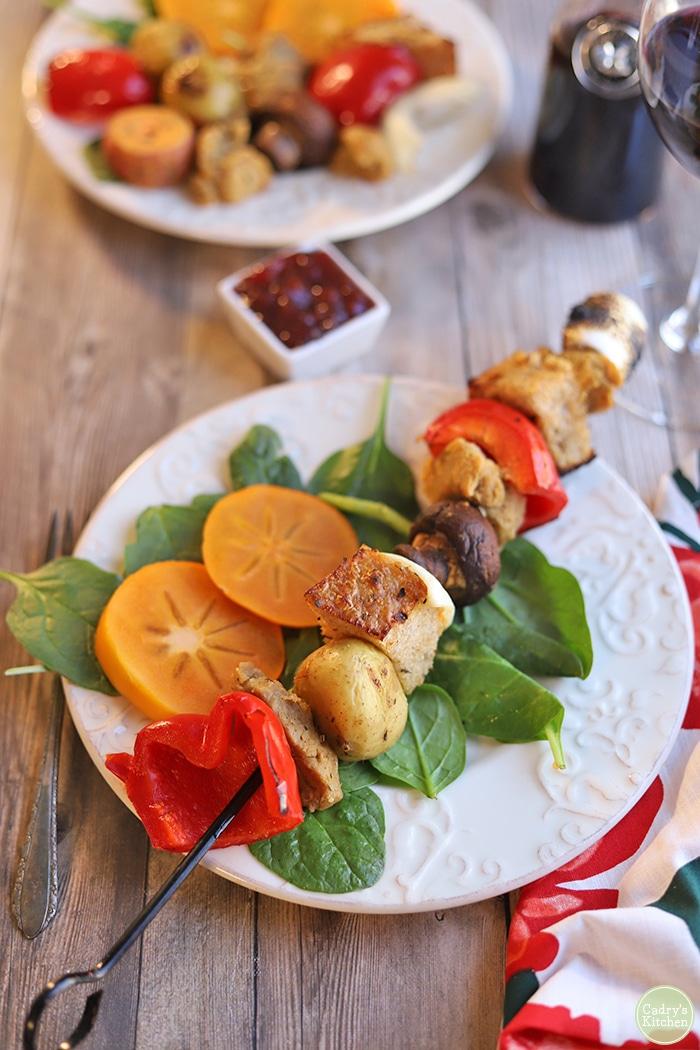 Veggie skewer on plate with salad.