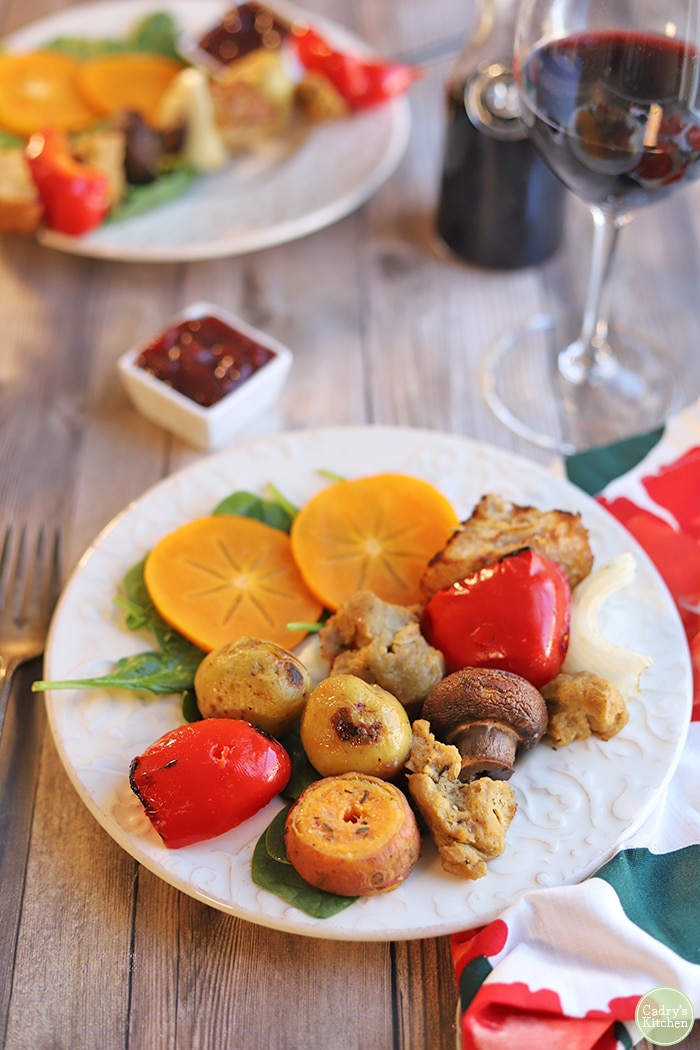 Potatoes, bell pepper, onion, and sweet potato on plate with salad.