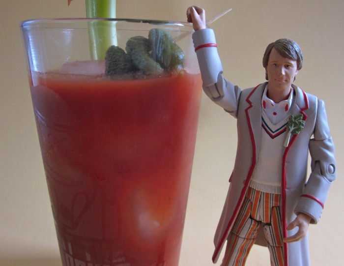 Peter Davison toy holding onto Bloody Mary in glass.
