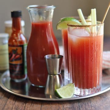 Bloody Mary drink on metal tray with ingredients.