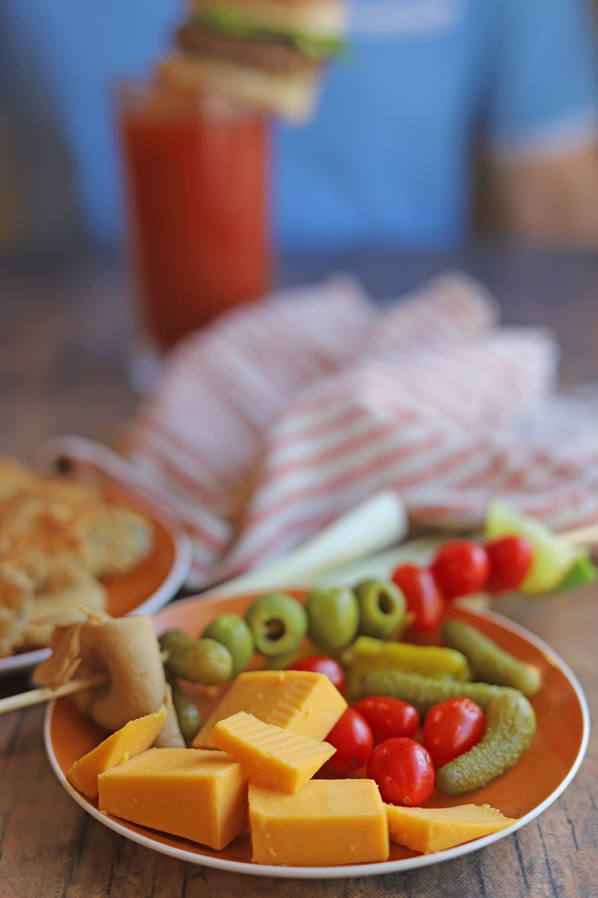 Garnishes on plate - vegan cheese cubes, skewers, tomatoes, and cornichons.