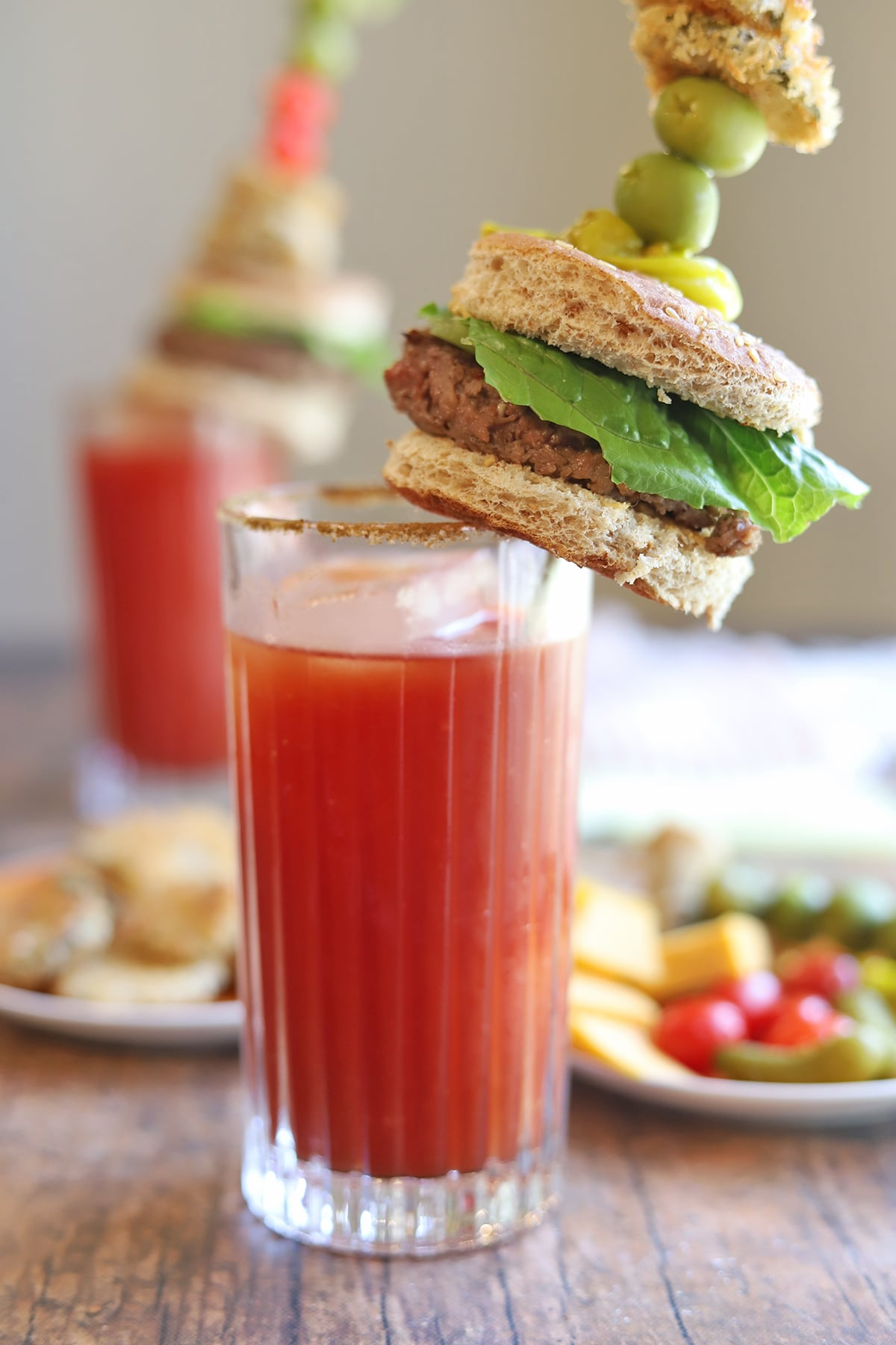 Veggie burger garnish on top of glass with Bloody Mary.