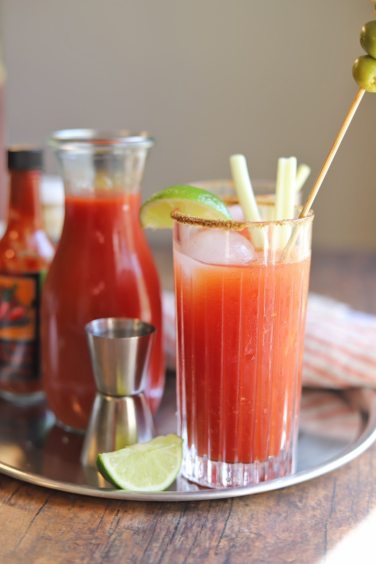 Bloody Mary drink on tray with tomato juice, jigger, lime, and hot sauce.