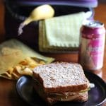 Vegan packed lunch ideas text + sandwich, chips, banana, and Klarbrum sparkling water.