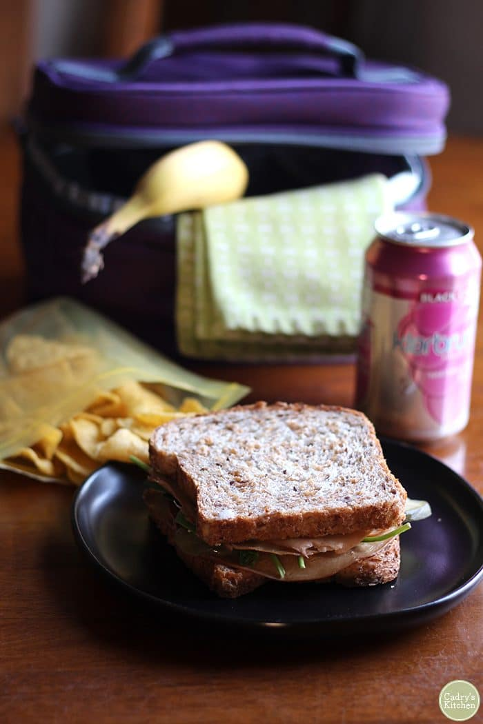 Vegan deli sandwich with potato chips, Klarbrum cherry sparkling water, banana, and chips.