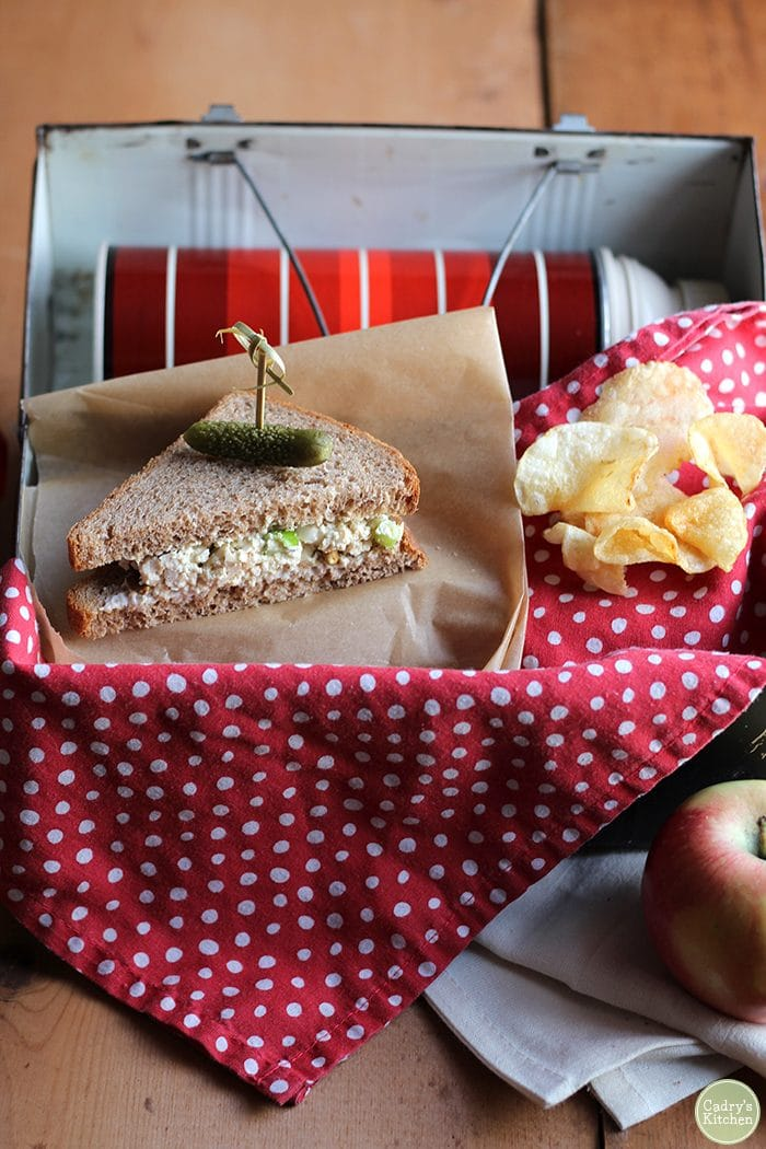 Vegan lunchbox with chickpea salad sandwich, potato chips, and apple.