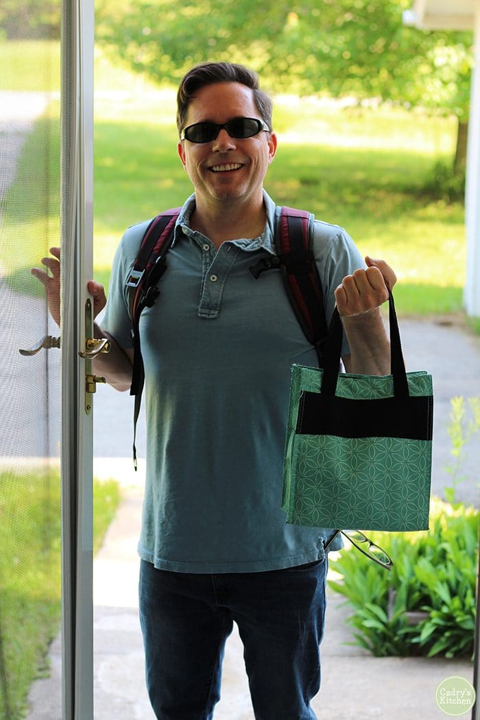 David holding lunch bag with vegan packed lunch at front door.