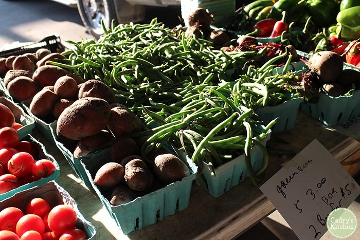 Green beans, tomatoes, and sweet potatoes on display at farmers market.