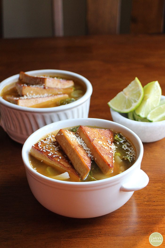 Spicy soup with tofu triangles in bowls by lime slices.