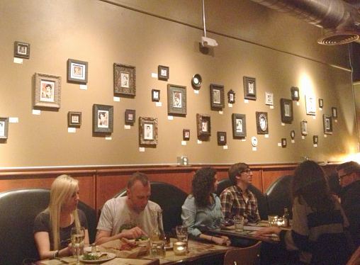 Framed pieces of art hanging on wall above diners.