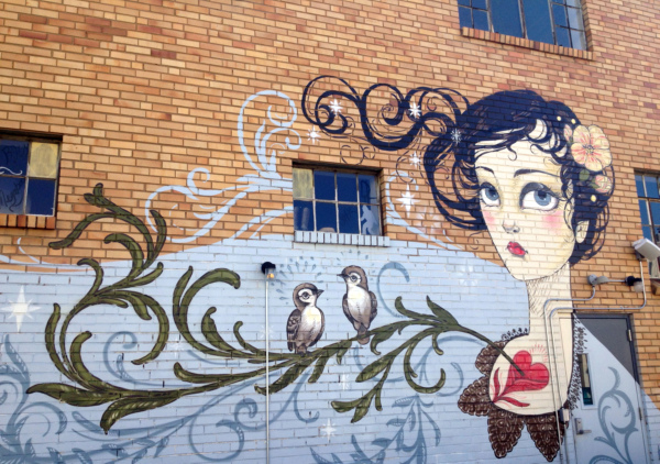 Mural of woman with heart on chest and birds on branch.