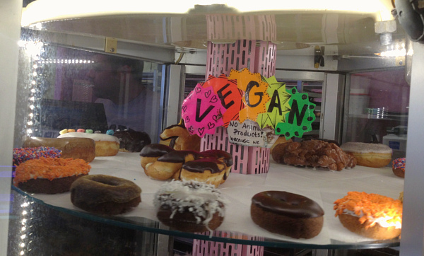 Donuts in display case with vegan sign.