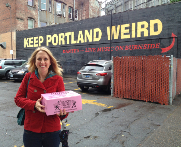 Cadry holding box of Voodoo Doughnuts in front of Keep Portland Weird sign.