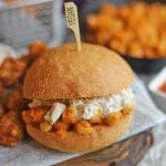 Text overlay: Buffalo chickpea sandwich with vegan blue cheese dressing. Sandwich on table with tater tots.