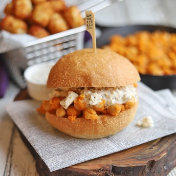 Buffalo chickpea sandwich on table with hot sauce.
