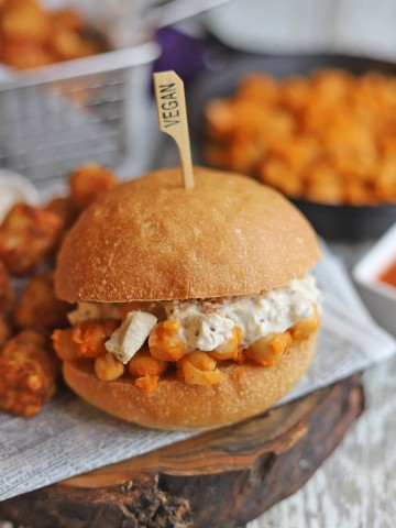 Buffalo chickpea sandwich topped with vegan blue cheese dressing.